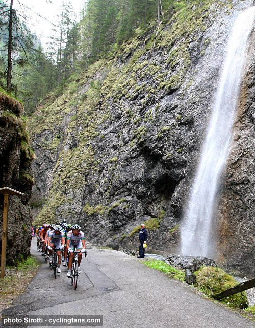 2008 Tour of Italy: The peloton rides by a waterfall during Stage 15